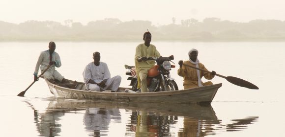 A boat taxi transports people and goods across the lake near Baga Sola, Chad