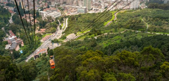 aerial view from Monserrate on top of the mountain where you can see downtown Bogota with tall buildings and road between the woods. Below we also see the cable car of the city arriving at its base.