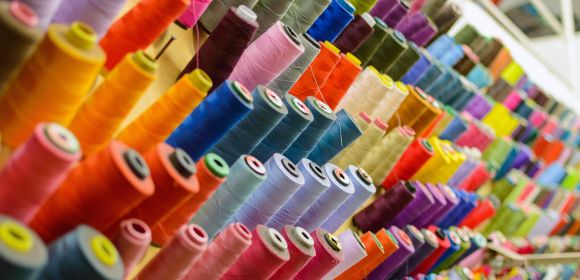 Colorful thread spools used in fabric and textile industry. The concept of sewing production