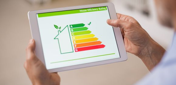 Hand holding digital tablet and looking at house efficiency rating. Detail of house efficiency rating on digital tablet screen.
