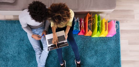 Young Couple Shopping Online On Laptop With Multi Colored Shopping Bags On Sofa
