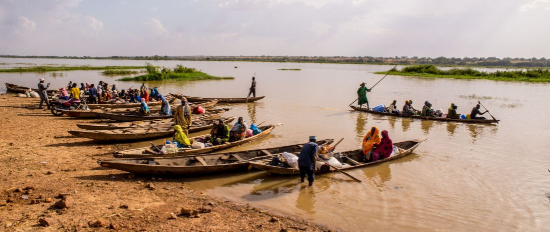Men ferry people and goods on dugouts on Niger River near Niamey, Niger.