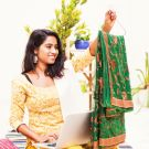 Woman using laptop and checking the saree that she got delivered from online store