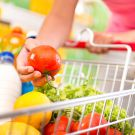 Full shopping cart at store with fresh vegetables and hands close-up