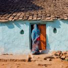 House of poor family and indian woman standing at the door of traditional style home, India.