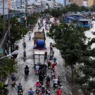 HO CHI MINH CITY, VIET NAM- OCT 18, 2016: Awful flooded street at Asian city, crowd of people ride motorcycle wade in water from tide on road, climate change make sea level rise, Vietnam