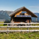 Wooden shepherd lodge with solar panels on a highland pasture with Alpine mountain landscape in Western Carinthia, Austria.