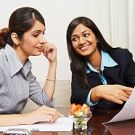 Two businesswomen sitting in an office and discussing documents