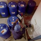 Man filling chemical storage containers