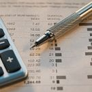 Close up of pen, calculator and financial pages