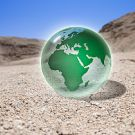 Green glass globe sitting in desert