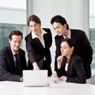 Four business people in a meeting using a laptop