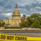 The US Capitol in Washington, DC. A yellow tape with the inscription Police Line Do Not Cross in the lower foreground.