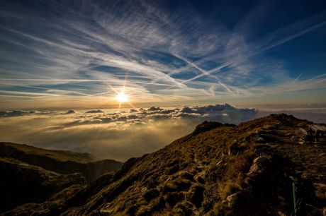 Mountain tops piercing through a cloudscape, with the sun peeking over the horizon and dramatically illuminating the clouds