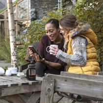 Two friends using mobile device and drinking tea after harvesting in the garden, London, UK, Europe,morning.