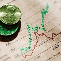 Green coins on stock chart, close-up