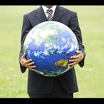 Businessman holding globe, mid section